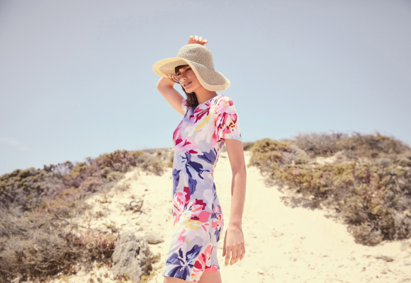 Woman wearing a floral dress and hat at the beach